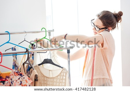 Smiling pretty young woman fashion designer in glasses checking new collection of clothes and talking on cell phone - stock photo