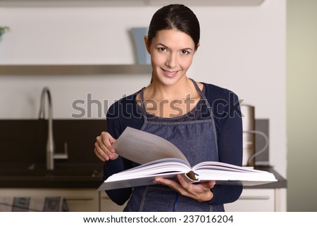 Smiling pretty young woman in an apron looking up a recipe in a large hardcover book as she stands in her kitchen preparing to cook the food for dinner or do a baking session