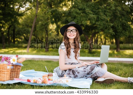 Smiling pretty young woman in hat and glasses using laptop on picnic in park - stock photo
