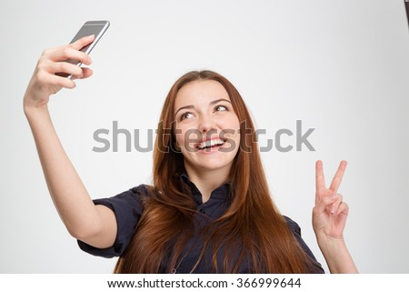 Smiling pretty young woman taking selfie with mobile phone and showing victory sign over white background - stock photo