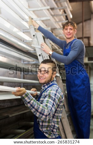 Smiling production workmen in uniform with different PVC window profiles indoor - stock photo