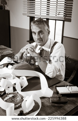 Smiling professional accountant working at desk, 1950s style office. - stock photo