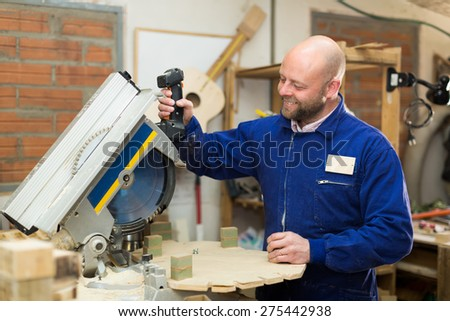 Smiling professional carpenter in blue robe cutting wooden workpiece with a power-saw