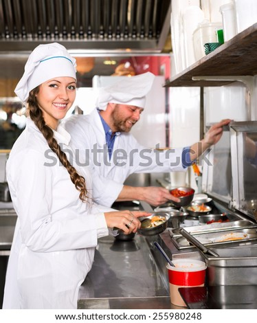Smiling professional chef and cook  working at take-away restaurant kitchen - stock photo