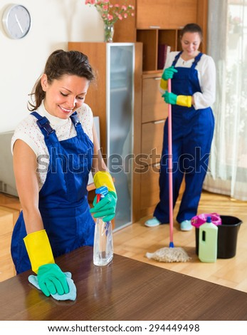 Smiling professional female cleaners washing apartment with rags and mop. Selective focus