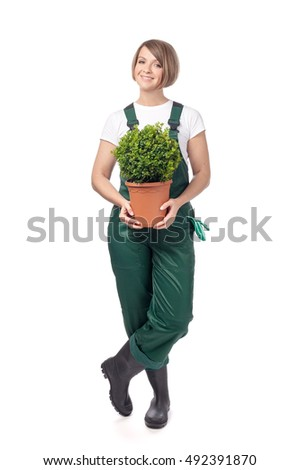 smiling professional gardener woman with tree in a pot isolated on white background. topiary art. gardening service and business concept