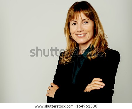 Smiling professional lady posing with arms crossed - stock photo