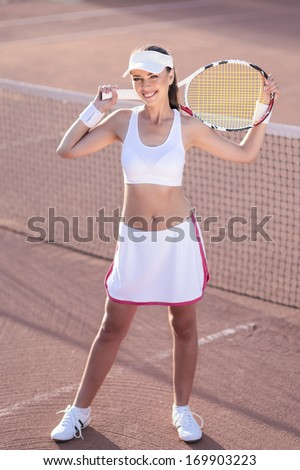 Smiling Professional Tennis Player Standing With Racquet on Tennis Court. Vertical Image