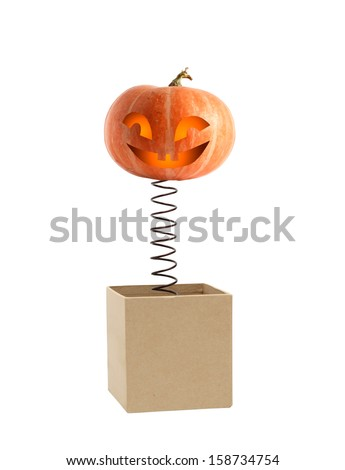 Smiling pumpkin head on metal spring jumping from box - stock photo