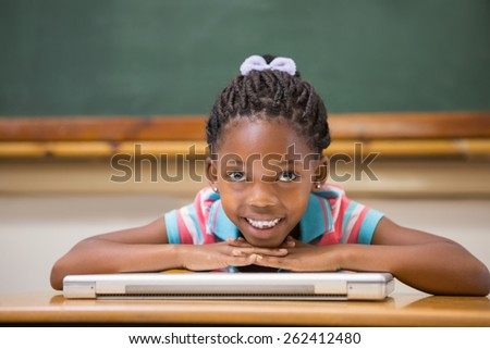 Smiling pupil sitting at her desk at the elementary school - stock photo