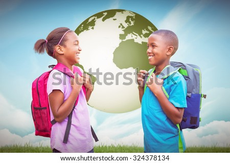 Smiling pupils against blue sky over green field - stock photo
