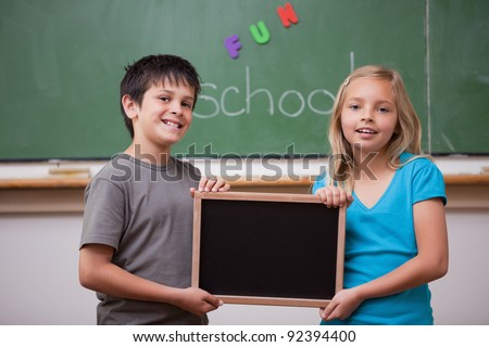 Smiling pupils holding a school slate in a classroom - stock photo