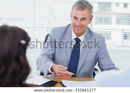 Smiling real estate agent completing contract with couple in bright office