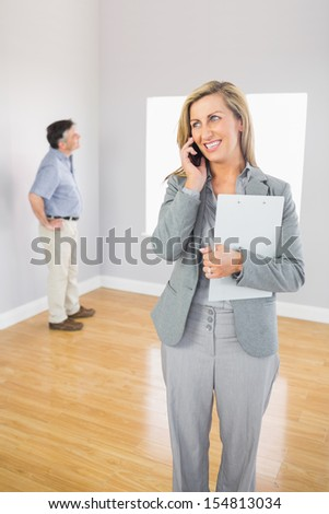 Smiling realtor calling someone with her mobile phone with buyer looking around the empty room - stock photo