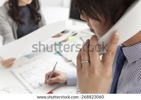 Smiling realtor calling someone with her mobile phone with buyer looking blueprint - stock photo