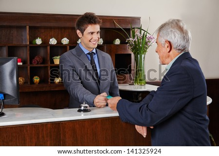 Smiling receptionist behind counter in hotel giving key card to senior guest - stock photo