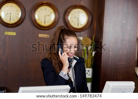 Smiling receptionist taking a telephone call while standing behind the counter in a hotel lobby or corporate venue - stock photo