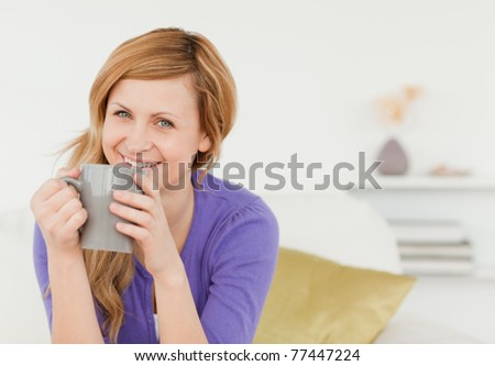 Smiling red-haired woman holding a cup of coffee and posing while sitting on a sofa in the living room