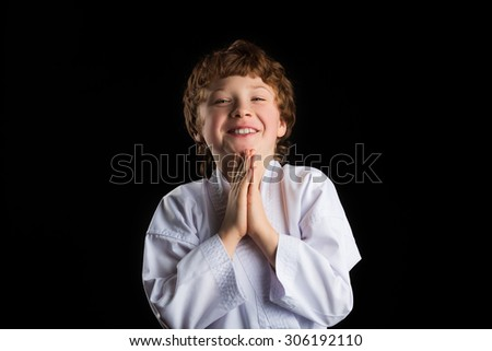 Smiling redhead caucasian karate boy in white kimono isolated on black background