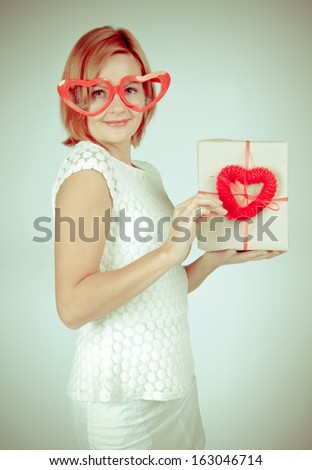 Smiling Redhead girl opening  gift box on Valentine's Day - stock photo