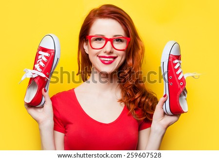 Smiling redhead girl with gumshoes on yellow background - stock photo