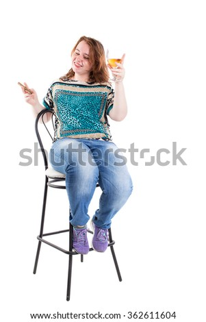 Smiling redhead plus size wreckled model sitting on the bar chair with glass of whiskey and cigar. Studio shot. Isolated on a white background.