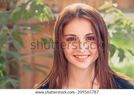 Smiling redhead teen. Front view closeup image of a  smiling teenage girl outdoors against old wood plank background with leaves