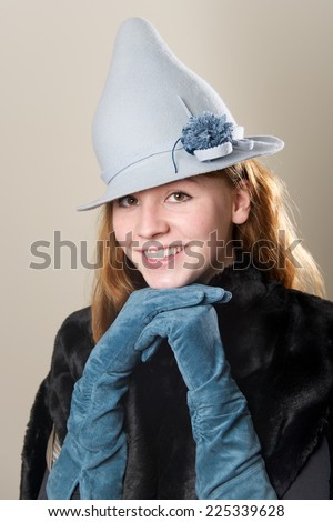 Smiling redhead with blue suede gloved hands