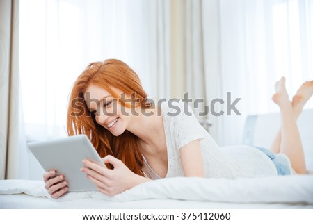 Smiling redhead woman using tablet computer on the bed at home - stock photo