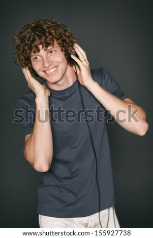 Smiling redheaded man in casual clothes with headphones looking out of frame - stock photo