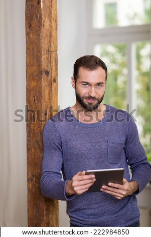Smiling relaxed bearded man in a casual t-shirt leaning against an old wooden door jamb holding a tablet computer in his hands and smiling at the camera - stock photo