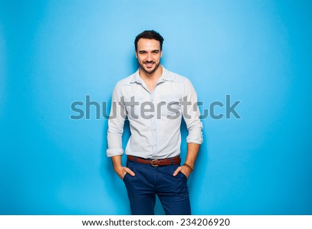 smiling relaxed handsome man with hands in pockets on blue background - stock photo