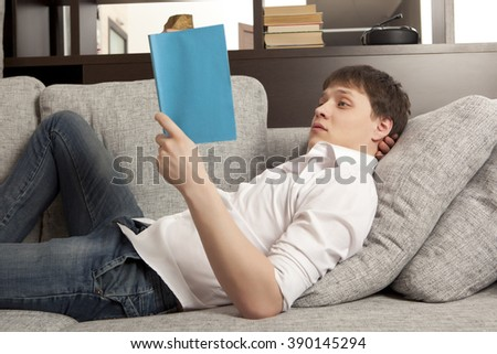 Smiling relaxed man reading a book lying on sofa - stock photo