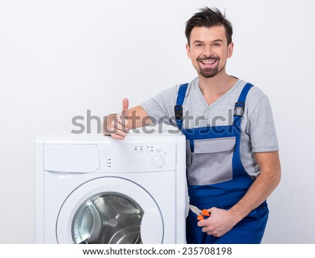 Smiling repairman is repairing a washing machine on the white background.