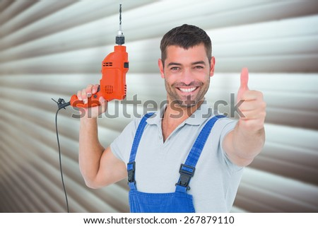 Smiling repairman with drill machine gesturing thumbs up against grey shutters - stock photo