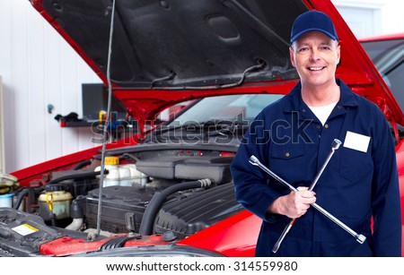 Smiling repairman with tire wrench in car repair service. - stock photo