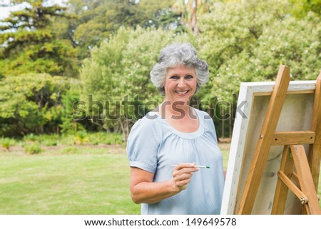 Smiling retired woman painting on canvas and looking at camera in the park - stock photo
