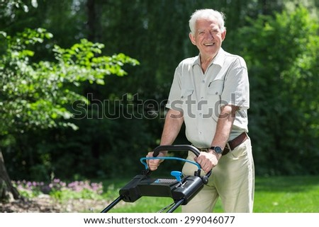 Smiling retiree cutting grass with lawn mower