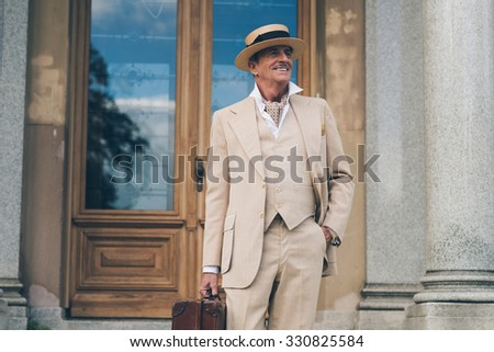 Smiling retro dandy standing at front door of his mansion. - stock photo