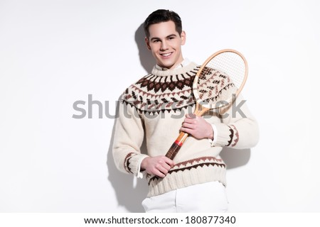 Smiling retro tennis fashion man holding a vintage wooden racket. Studio shot against white.