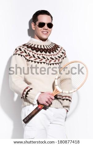 Smiling retro tennis fashion man with sunglasses holding a vintage wooden racket. Studio shot against white. - stock photo
