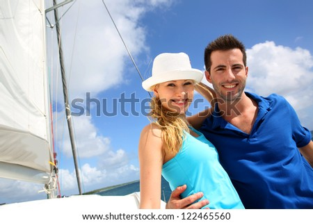 Smiling rich young couple on a sailboat in Caribbean sea - stock photo