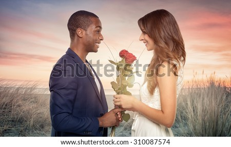 Smiling romantic handsome young African man proposing to his sweetheart as he clutches a bunch of long stemmed red roses in his hand, sideview in the sunset on a beach