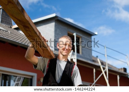 Smiling roofer carrying a wood plank over his shoulder - stock photo
