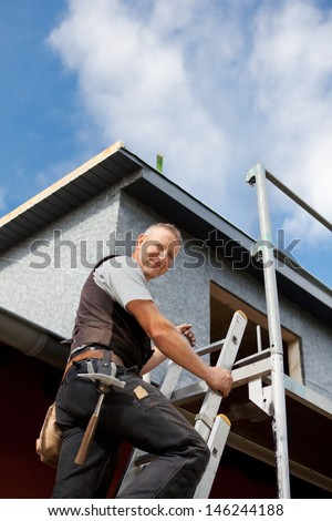 Smiling roofer climbing a ladder at the construction site - stock photo