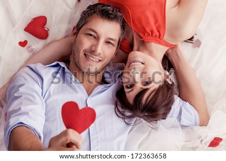smiling rose bed lying lovers - stock photo