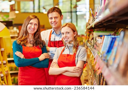 Smiling sales team staff in supermarket with their arms crossed - stock photo