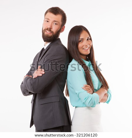 Smiling sales team with arms folded standing back to back against a white background - stock photo