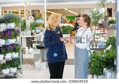 Smiling salesgirl looking at female customer smelling flowers in shop - stock photo