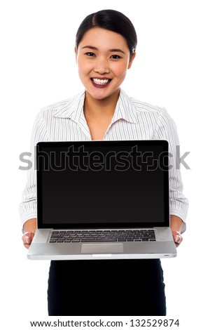 Smiling salesgirl presenting brand new laptop for sale. Business and technology concept.